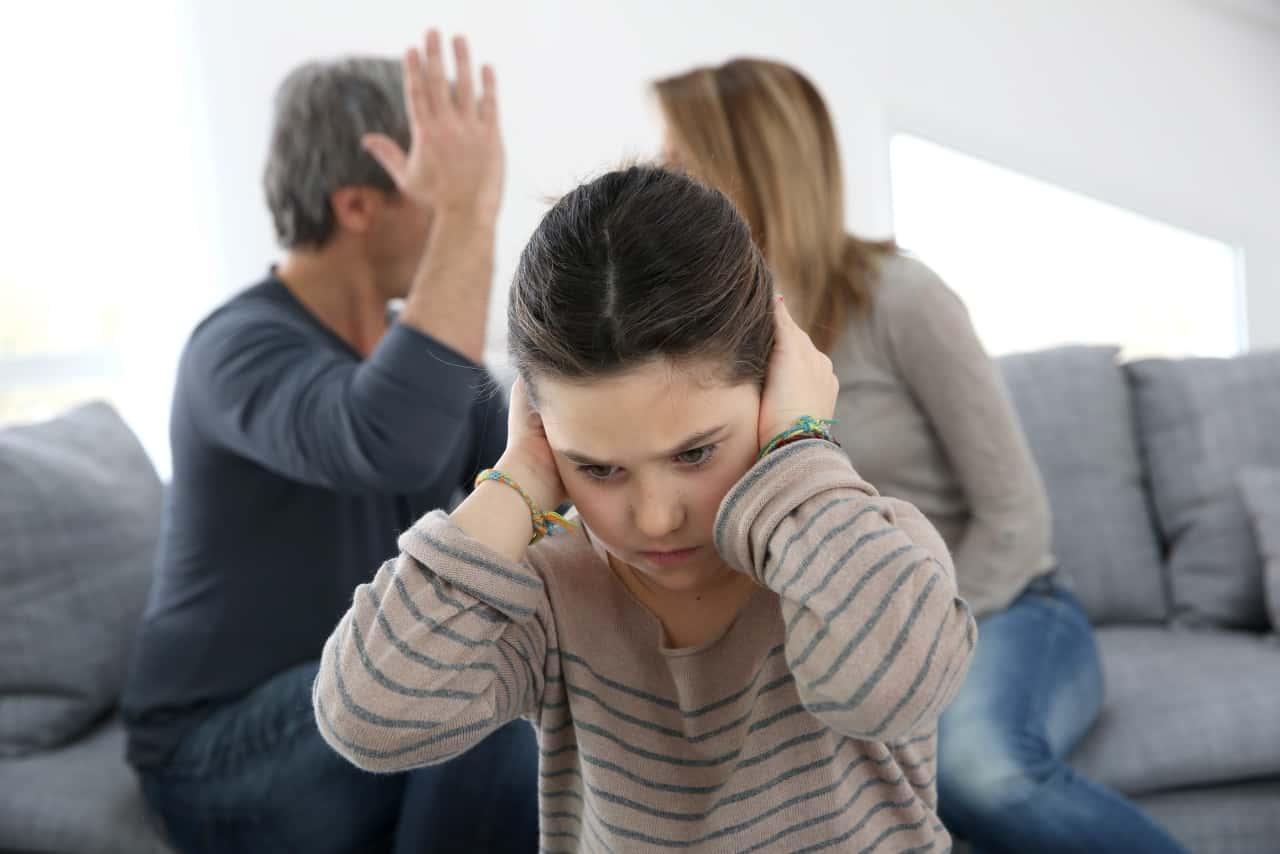 הורים צועקים אחד על השני והילד שם ידיים על האוזניים