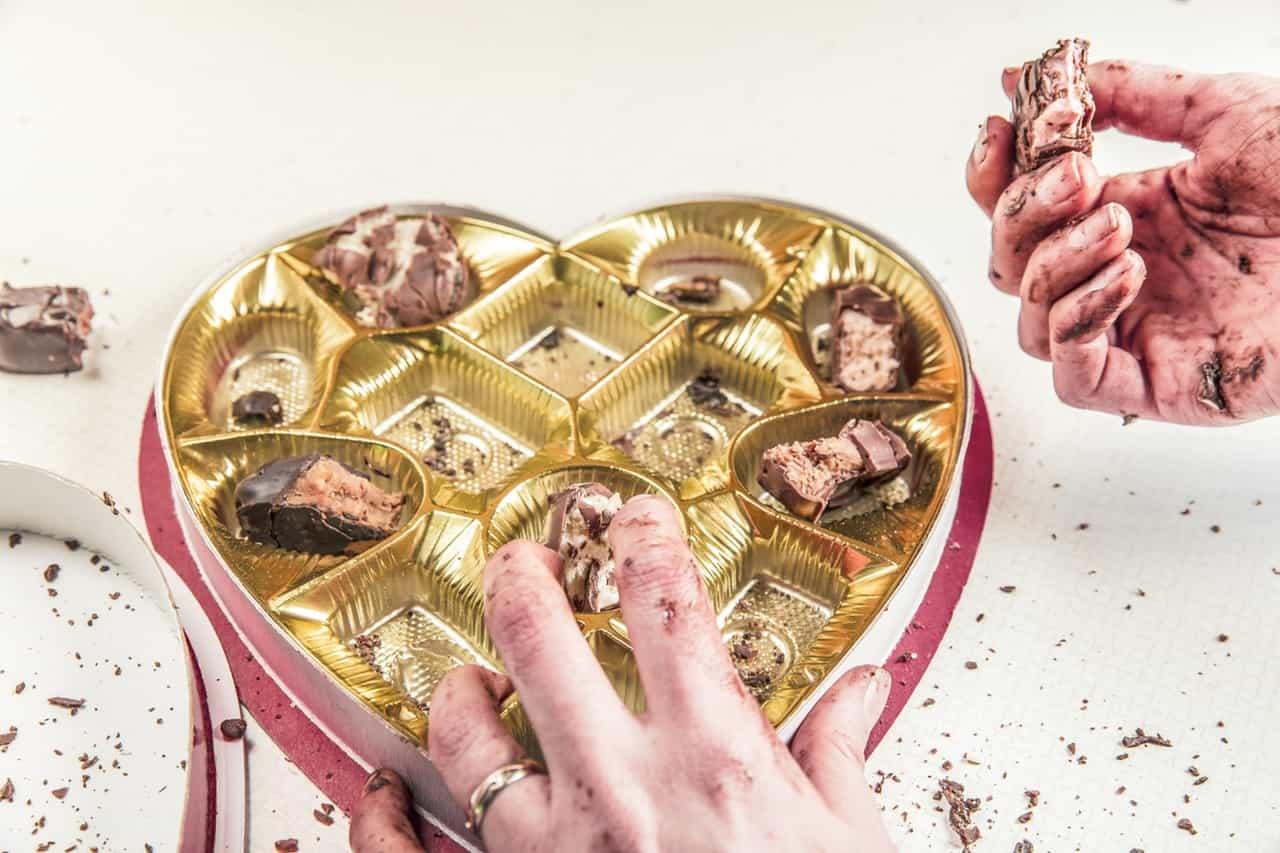 ידיים אוכלות מקופסות שוקולדים