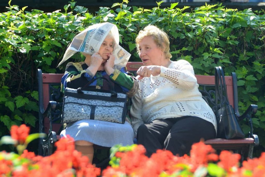שתי נשים מבוגרות יושבות על ספסל ומדברות