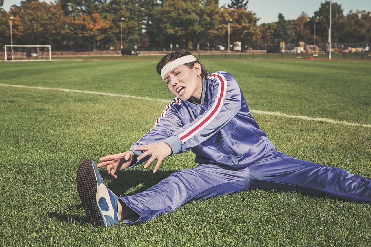בחורה ספורטיבית מתקשה בביצוע מתיחות